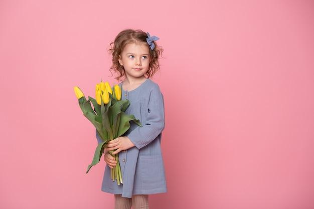 Piękna mała blondynka w niebieskiej sukience z bukietem żółtych tulipanów na różowym tle