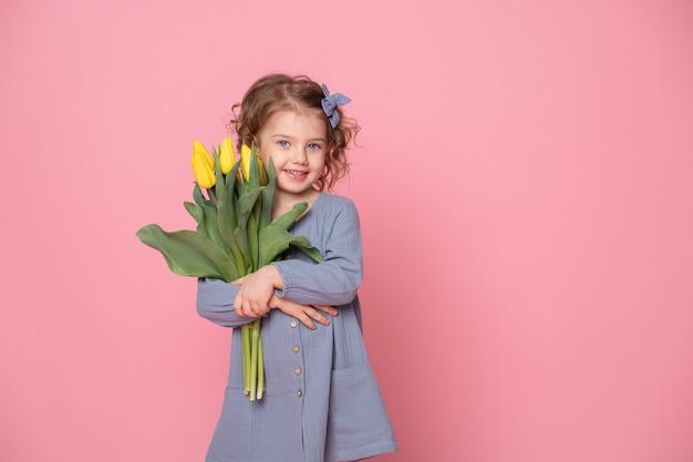 Piękna mała blondynka w sukience blu z bukietem żółtych tulipanów na różowym tle z miejscem na tekst.