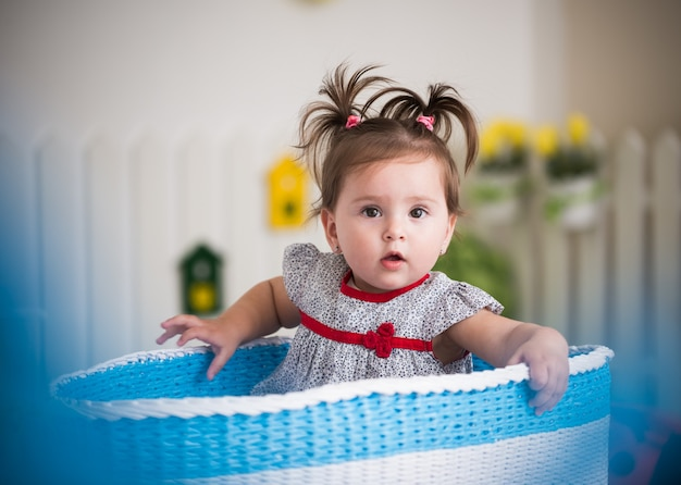 Piękna mała brązowooka dziewczynka siedzi w dużym koszu na zabawki w swoim przytulnym dziecięcym pokoju.