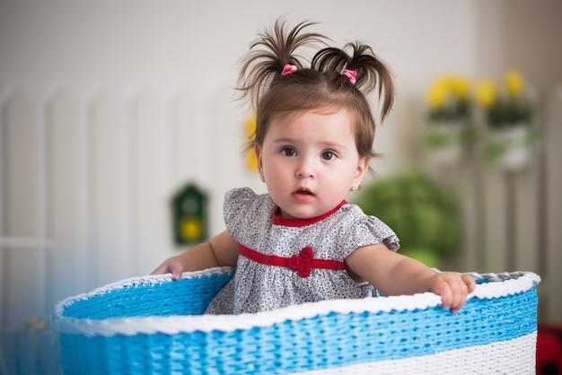 Piękna mała brązowooka dziewczynka siedzi w dużym koszu na zabawki w swoim przytulnym pokoju dziecięcym