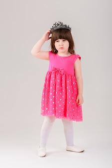 Piękna mała brunetka dziewczynka w różowej sukience księżniczki z koroną na szarym tle. słodkie dziecko