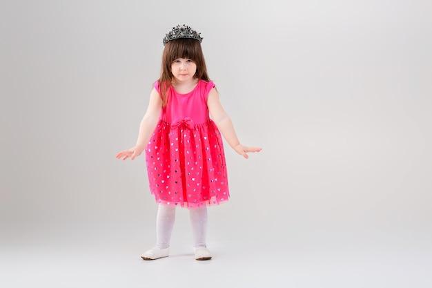 Piękna mała brunetka dziewczynka w różowej sukience księżniczki z koroną próbuje dygać na szarym tle. słodkie dziecko