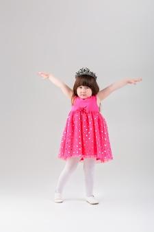 Piękna mała brunetka dziewczynka w różowej sukience księżniczki z koroną z rozpostartymi ramionami na szarym tle. słodkie dziecko