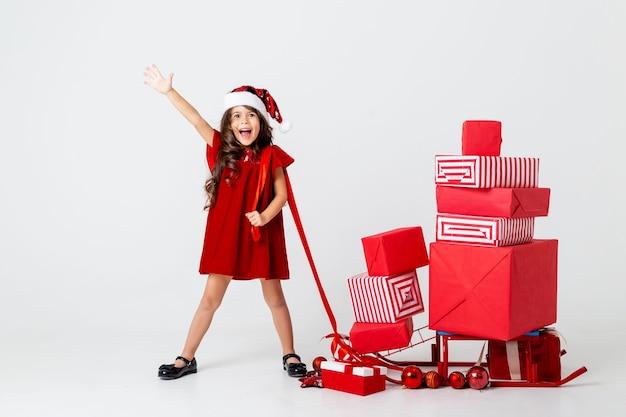 Piękna mała brunetka w stroju świętego mikołaja niesie prezenty świąteczne na saniach miejsce na teksa