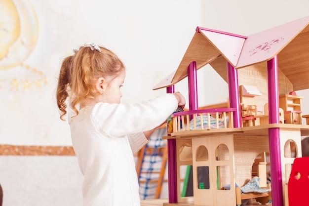 Piękna mała dziewczynka bawi się drewnianym domkiem dla lalek