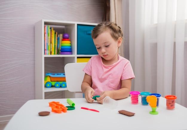 Piękna mała dziewczynka bawi się gliną przy stole w pokoju