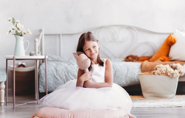 Piękna mała dziewczynka bawi się zabawką na podłodze w jasnym pokoju. szczęśliwy, uśmiechnięty dziecko