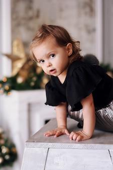 Piękna mała dziewczynka bawić się blisko choinki w domu