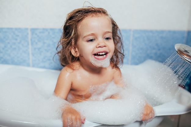 Piękna mała dziewczynka bierze skąpanie w domu.