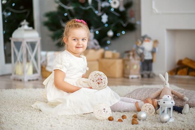 Piękna mała dziewczynka czeka na cud w ozdób choinkowych