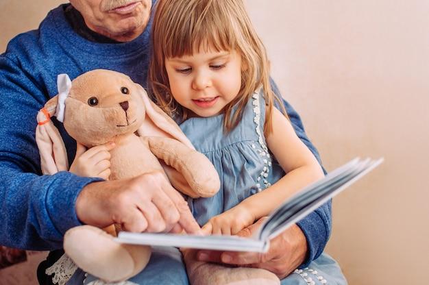 Piękna mała dziewczynka czytanie książki z dziadkiem w domu