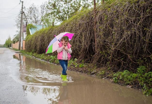 Piękna mała dziewczynka idzie ulicą z kolorowym parasolem i zielonymi gumowymi butami w kałużach. dziewczyna idzie ulicą i patrzy na kałuże.