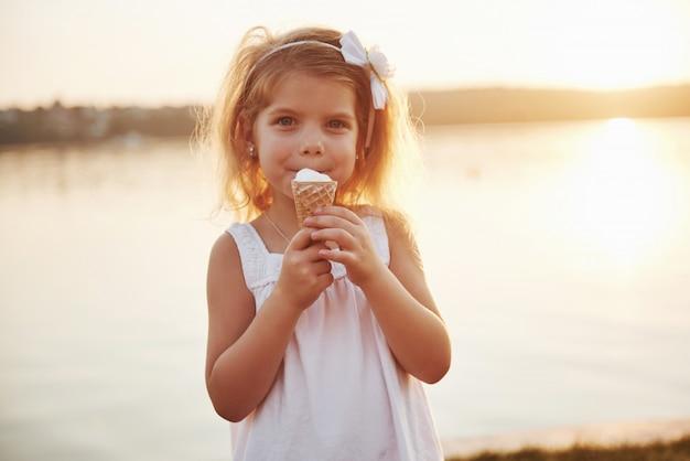 Piękna mała dziewczynka je lody w pobliżu wody