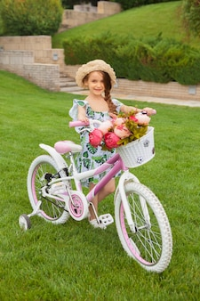 Piękna mała dziewczynka jedzie bicykl przez parka. natura, styl życia