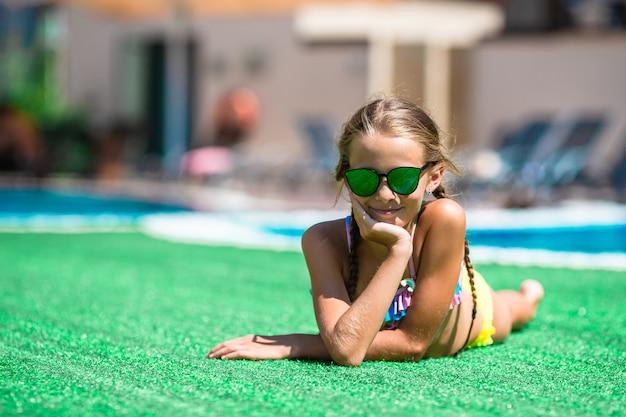 Piękna mała dziewczynka ma zabawę blisko plenerowego basenu