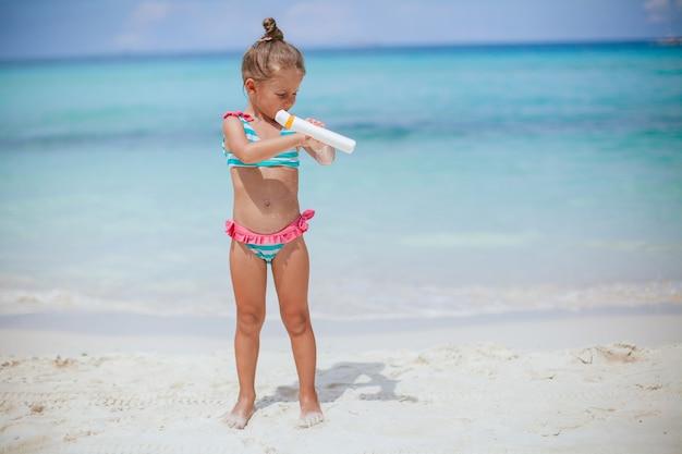 Piękna mała dziewczynka na plaży z butelką kremu do opalania. ochrona przed słońcem
