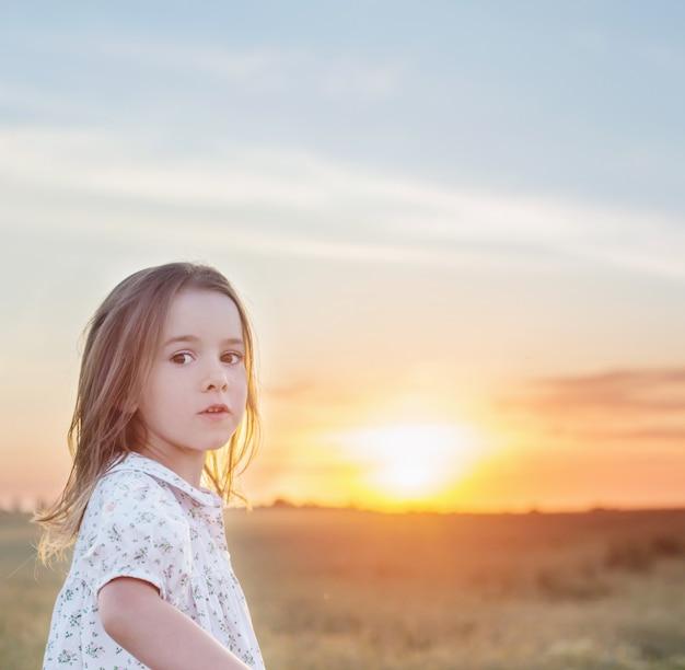 Piękna mała dziewczynka na polu tła o zachodzie słońca