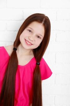Piękna mała dziewczynka na ścianie z cegieł