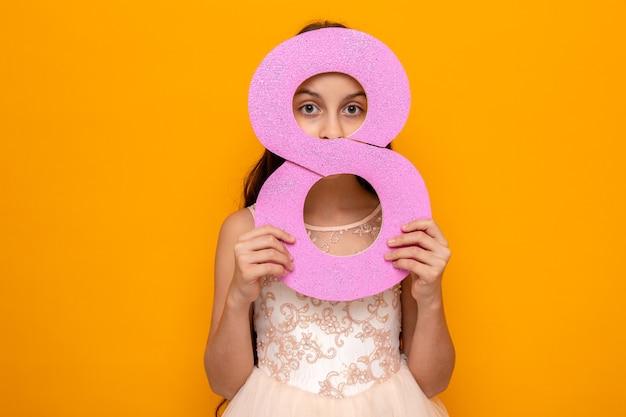 Piękna mała dziewczynka na szczęśliwy dzień kobiet trzymająca i zakrytą twarz z numerem osiem