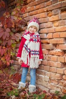 Piękna mała dziewczynka na tle starego ceglanego muru jesienią