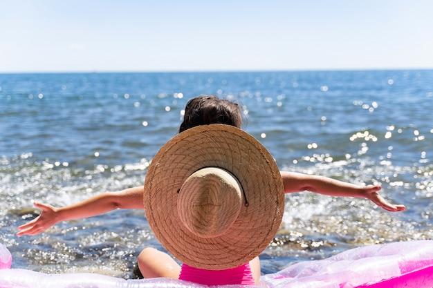 Piękna mała dziewczynka nad morzem w kapeluszu patrzy na morze i ręce