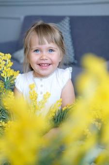 Piękna mała dziewczynka o niebieskich oczach i jasnych warkoczach się uśmiecha. na pierwszym planie żółte kwiaty mimosa.