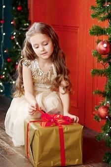 Piękna mała dziewczynka otwiera bożenarodzeniowego prezenta pudełko. obchody bożego narodzenia i nowego roku.