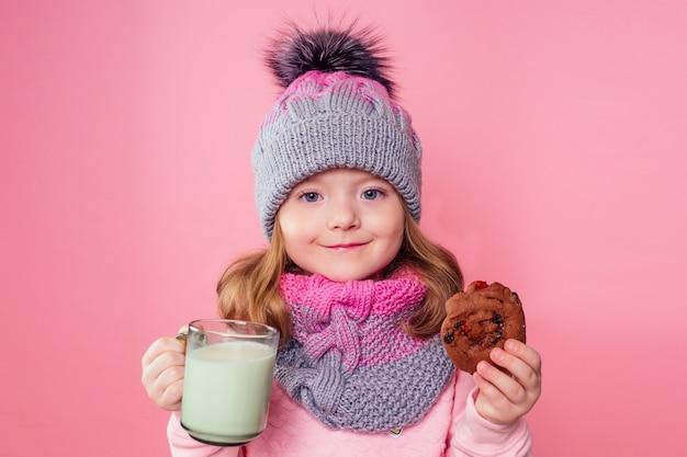 Piękna mała dziewczynka pije mleko i zjada ciasteczka w czapce i szaliku na różowym tle w studio, noc bożego narodzenia