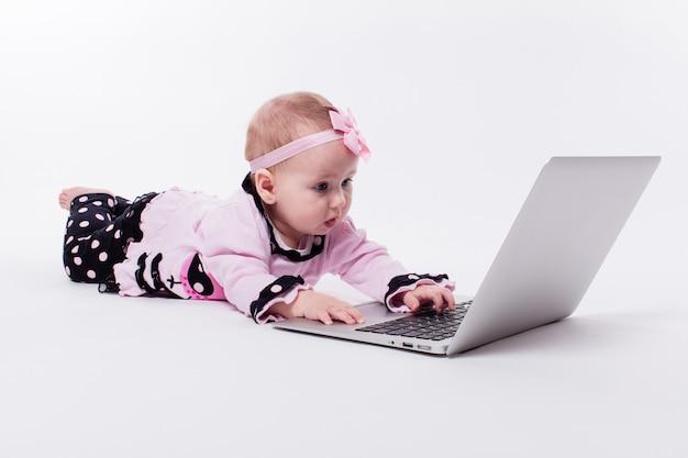 Piękna mała dziewczynka pisze lub bawić się na laptopie