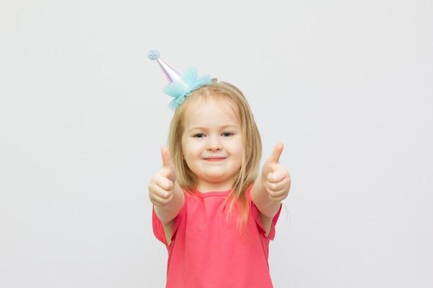 Piękna mała dziewczynka pokazuje palec na znak, że wszystko jest w porządku