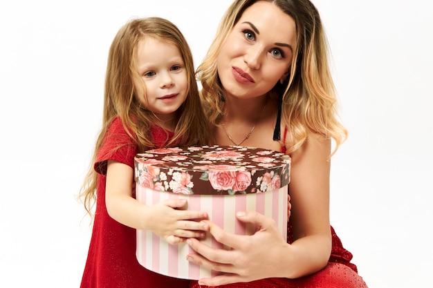 Piękna mała dziewczynka pozuje na białym tle z młodą matką, trzymając fantazyjne pudełko, dając ci go na urodziny