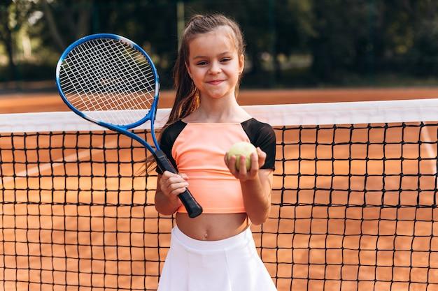 Piękna mała dziewczynka pozuje na tenisowym sądzie z kantem i tenisową piłką