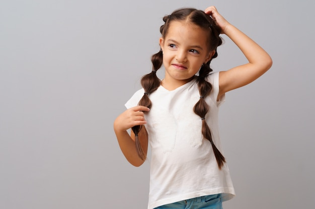 Piękna mała dziewczynka pozuje nad szarym tłem