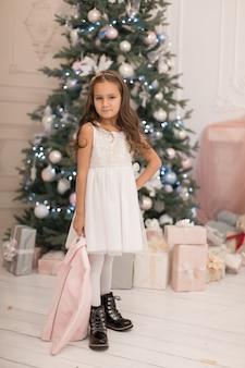 Piękna mała dziewczynka pozuje w pobliżu choinki