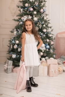 Piękna mała dziewczynka pozuje w pobliżu choinki.