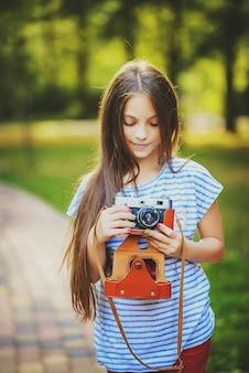 Piękna mała dziewczynka robi zdjęcie aparatem vintage w zielonym, słonecznym lesie