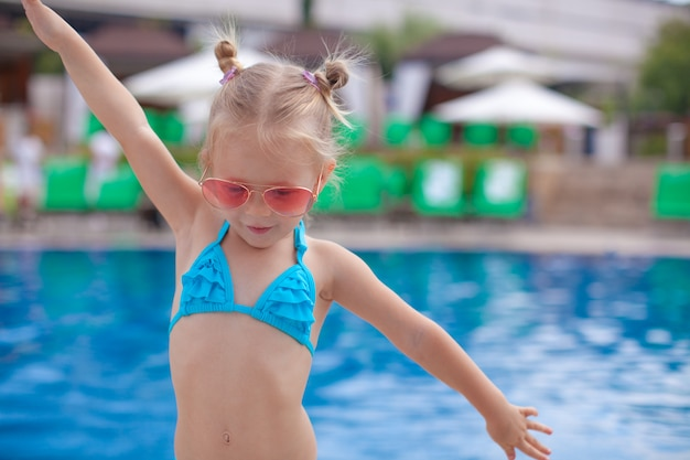 Piękna mała dziewczynka rozprzestrzenia jej ręki stoi blisko pływackiego basenu