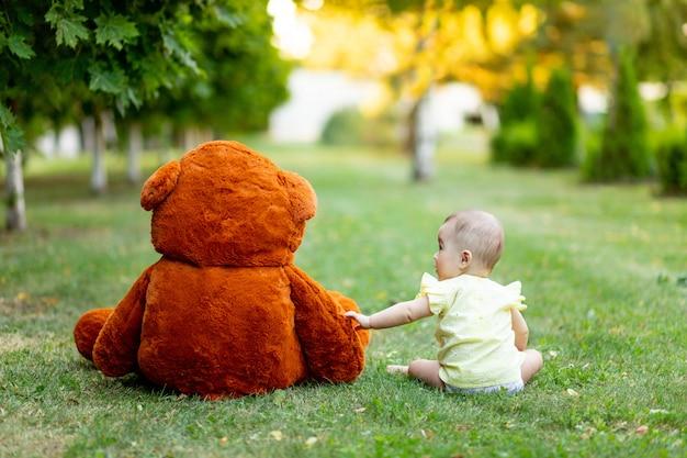 Piękna mała dziewczynka siedzi na zielonej trawie z powrotem z wielkim misiem w żółtej letniej sukience