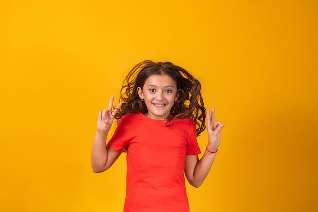 Piękna mała dziewczynka skoki na żółtym tle z miejscem na tekst.