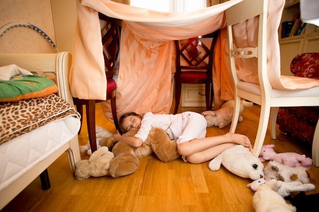 Piękna mała dziewczynka śpi na misiu w sypialni