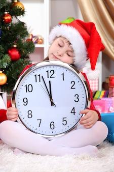 Piękna mała dziewczynka śpi w oczekiwaniu na nowy rok w świątecznie urządzonym pokoju