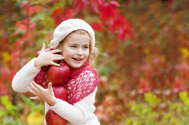 Piękna mała dziewczynka trzyma jabłka w jesiennym ogrodzie. . mała dziewczynka gra w sadzie jabłkowym. maluch jedzenie owoców na jesienne zbiory. zabawa na świeżym powietrzu dla dzieci. zdrowe odżywianie