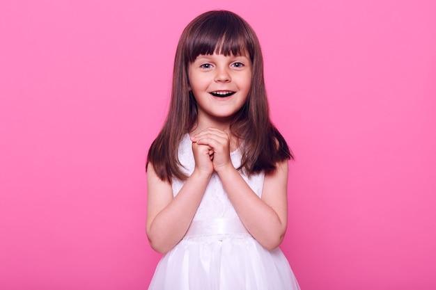 Piękna mała dziewczynka ubrana w białą sukienkę, patrząc z podniecenia z przodu, zdumiona czymś, co widzi, ubrana w białą sukienkę, odizolowana na różowej ścianie