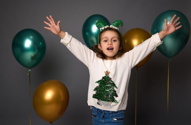 Piękna mała dziewczynka ubrana w biały świąteczny sweter i obręcz elfów, podnosi ręce do góry stojąc przed kolorowymi złotymi i zielonymi pięknymi balonami na białym tle nad szarym tłem z miejsca kopiowania