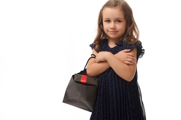 Piękna mała dziewczynka ubrana w stylową suknię wieczorową patrzy w kamerę, pozowanie ze skrzyżowanymi rękami i pakietem zakupów, na białym tle nad białym tle z miejsca kopiowania. koncepcja czarnego piątku