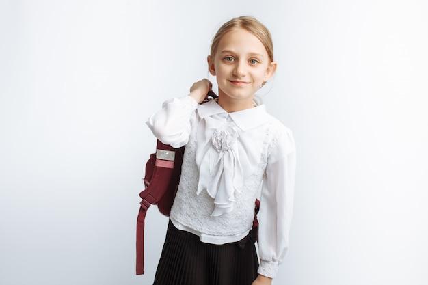 Piękna mała dziewczynka, uczennica, biała ściana