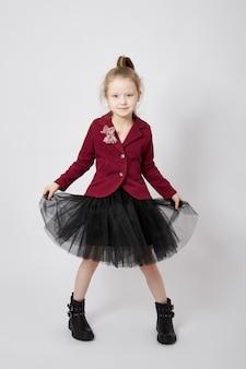 Piękna mała dziewczynka uśmiecha się, dziecko w jesienne ubrania pozuje na białym tle