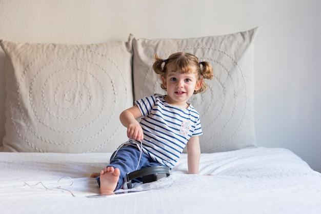 Piękna mała dziewczynka używa pastylkę i trzymający hełmofony na łóżku. dom, wnętrze. styl życia