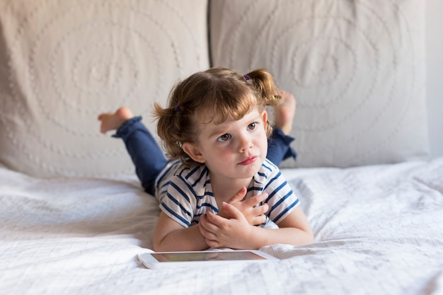 Piękna mała dziewczynka używa pastylkę na łóżku. dom, wnętrze. styl życia
