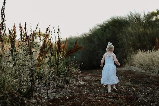 Piękna mała dziewczynka w białej sukience spacerująca po wiejskiej drodze o zachodzie słońca